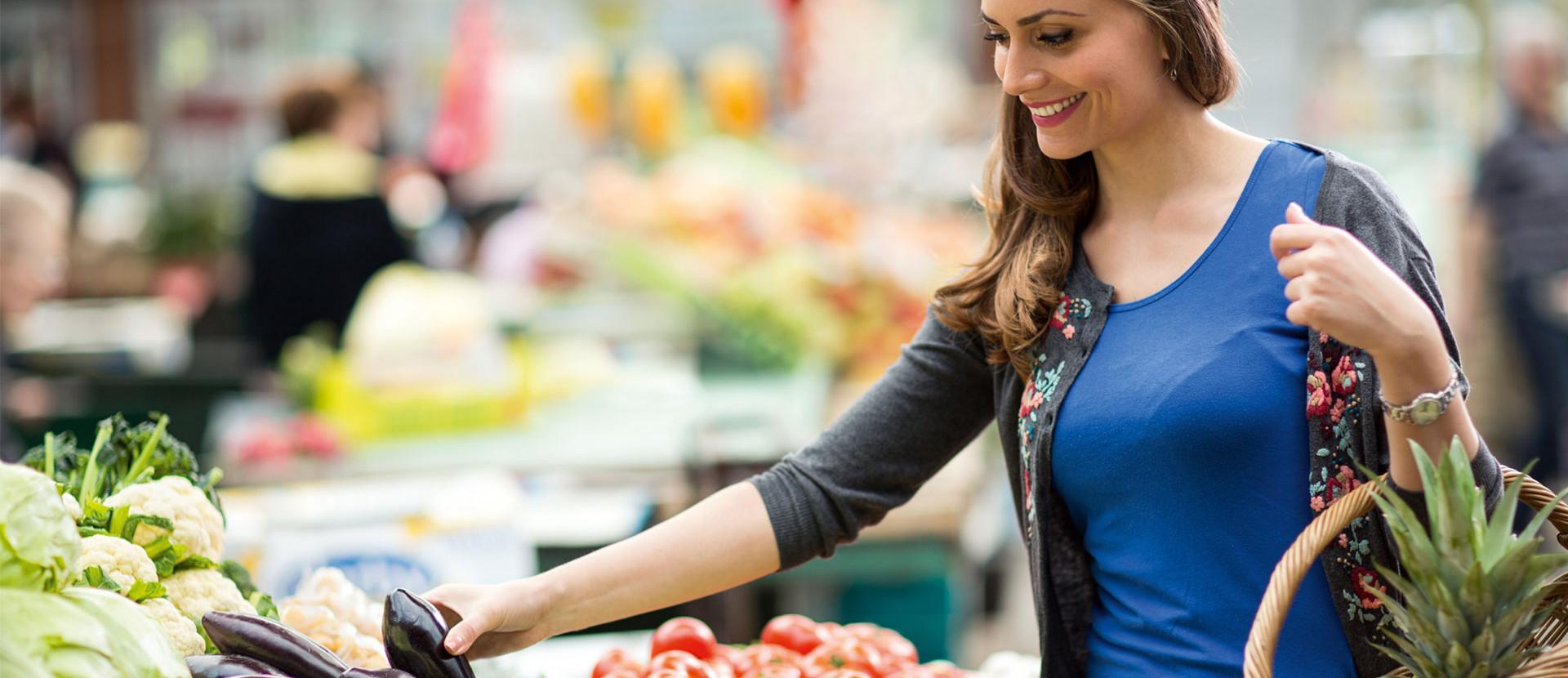 Frau mit Korb in einer Obst- und Gemüseabteilung