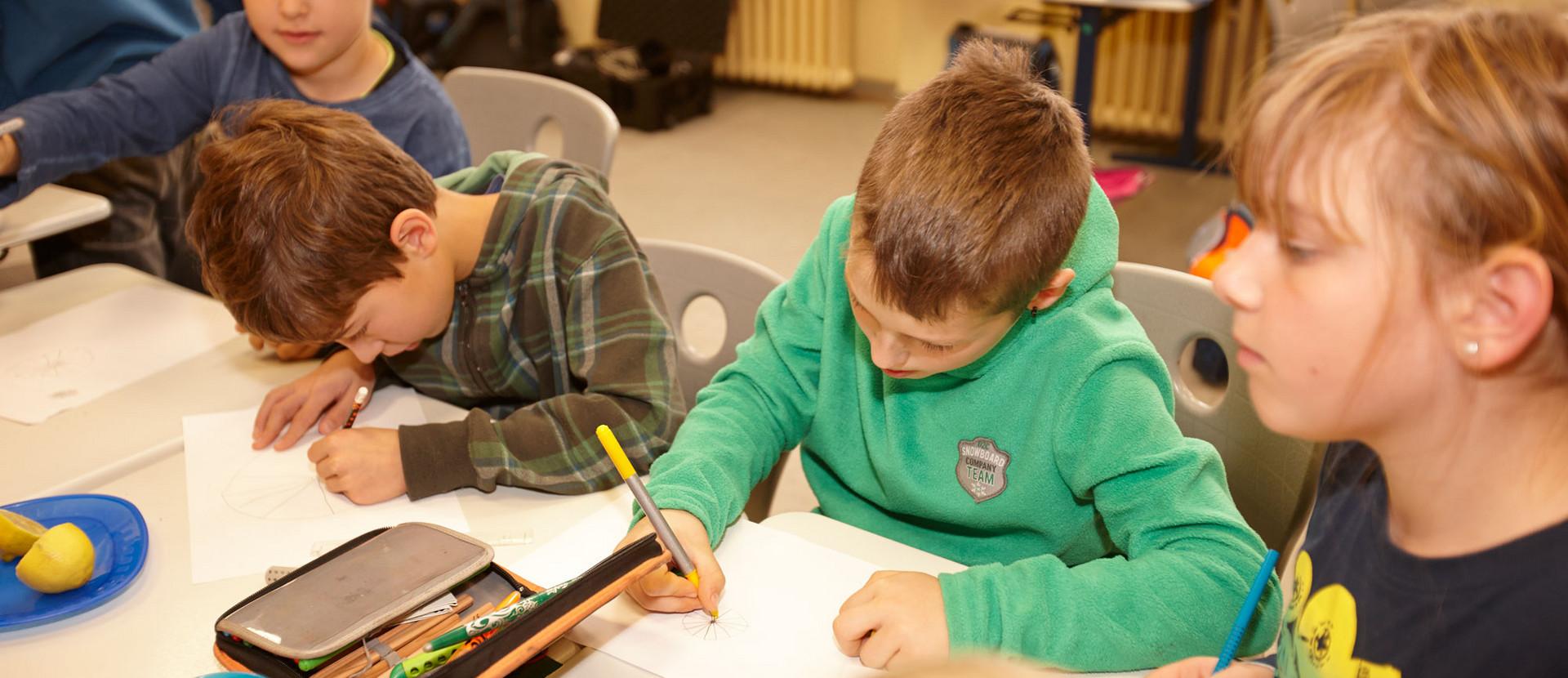 Kinder malen am Tisch
