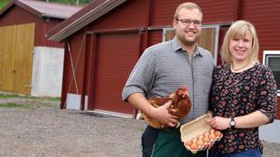 Betriebsleitung mit Huhn und Eiern vor Stall