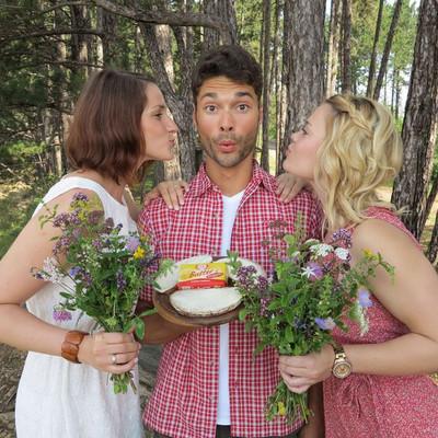 zwei Frauen mit Blumensträußen stehen rechts und links neben einem Mann in einem Wald