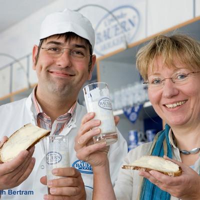 Frau und Mann mit Glas Milch und Butterbroten in den Händen