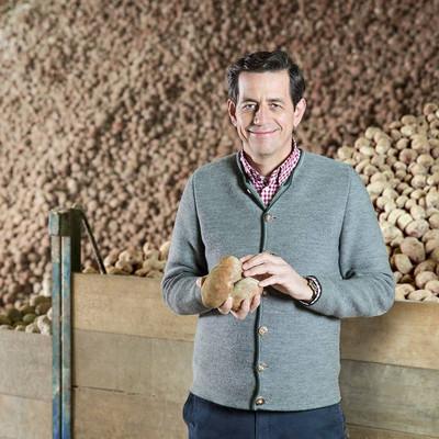 Mann steht im Kartoffellager