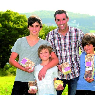 Mann steht mit drei Söhnen auf einer Wiese und sie haben Packungen mit Pilzen in den Händen