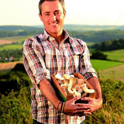 Mann steht auf einer Wiese und hat einen Karton Pilze in den Händen