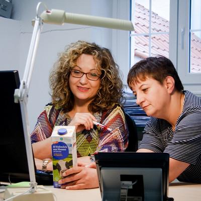zwei Frauen schauen am Schreibtisch eine Packung Milch an
