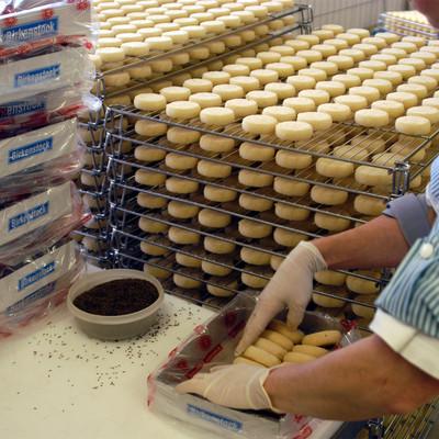 Fabrikarbeiterin verpackt hessischen Handkäse aus der Palette