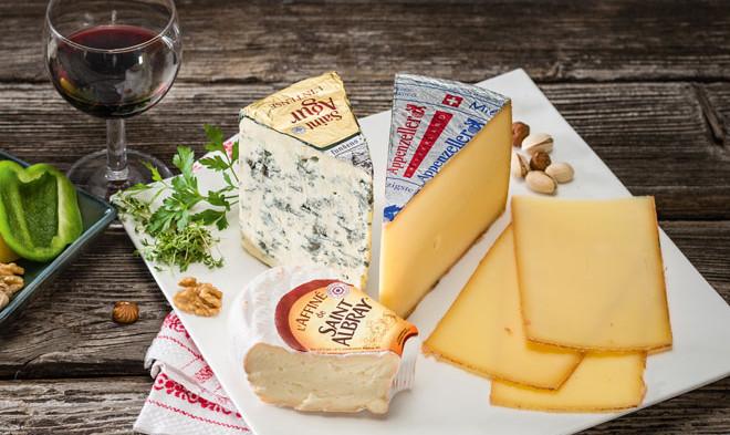Käse auf einem Teller und ein Glas Wein