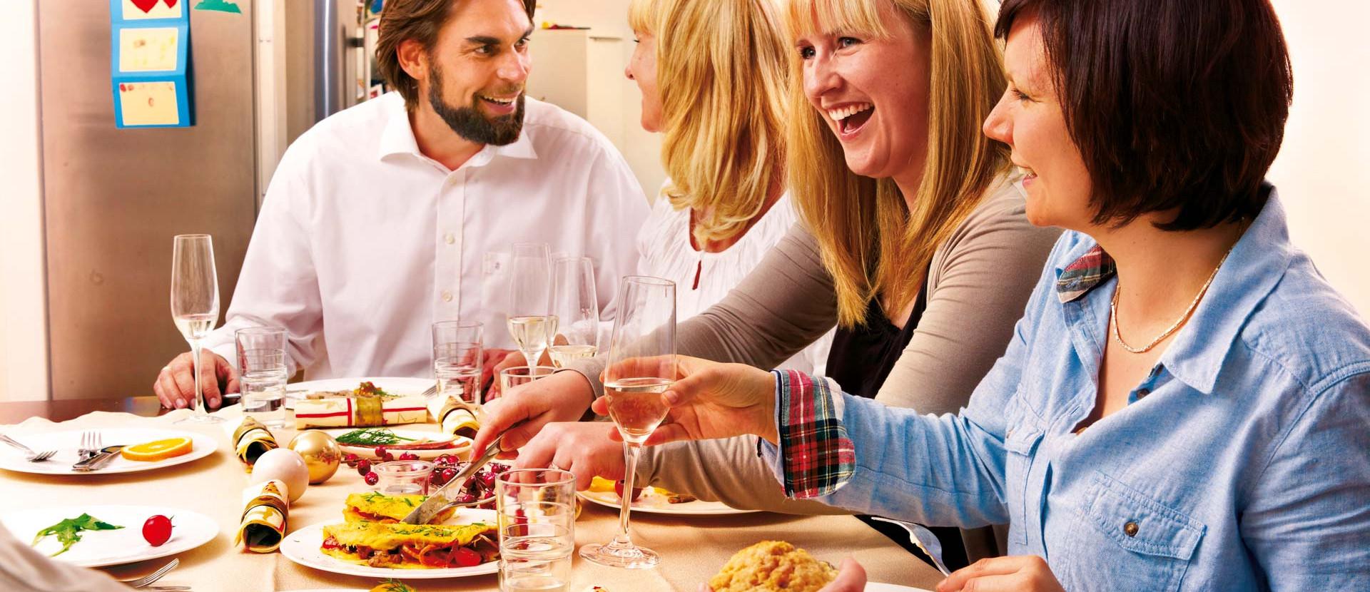 drei Frauen und ein Mann sitzen beim Adventsfrühstück