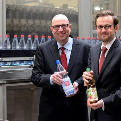Dr Ziegler und Christian Schindel stehen mit einer Flasche in der Hand neben der Abfüllanlage