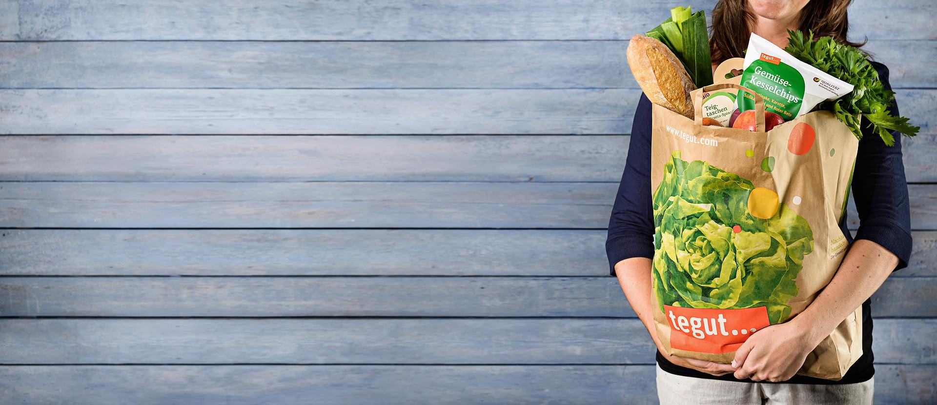 Frau mit einer lecker gefüllten Lebensmitteltüte steht vor einer Holzwand.
