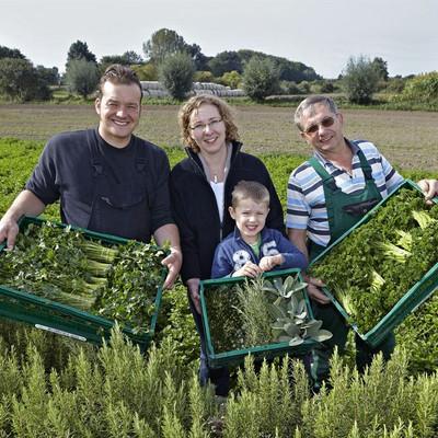 Familie auf einem Feld mit Kiste gefüllt mit Kräutern