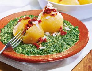 Pesto-rosso-Klöße mit würzigen Tomaten auf Spinat
