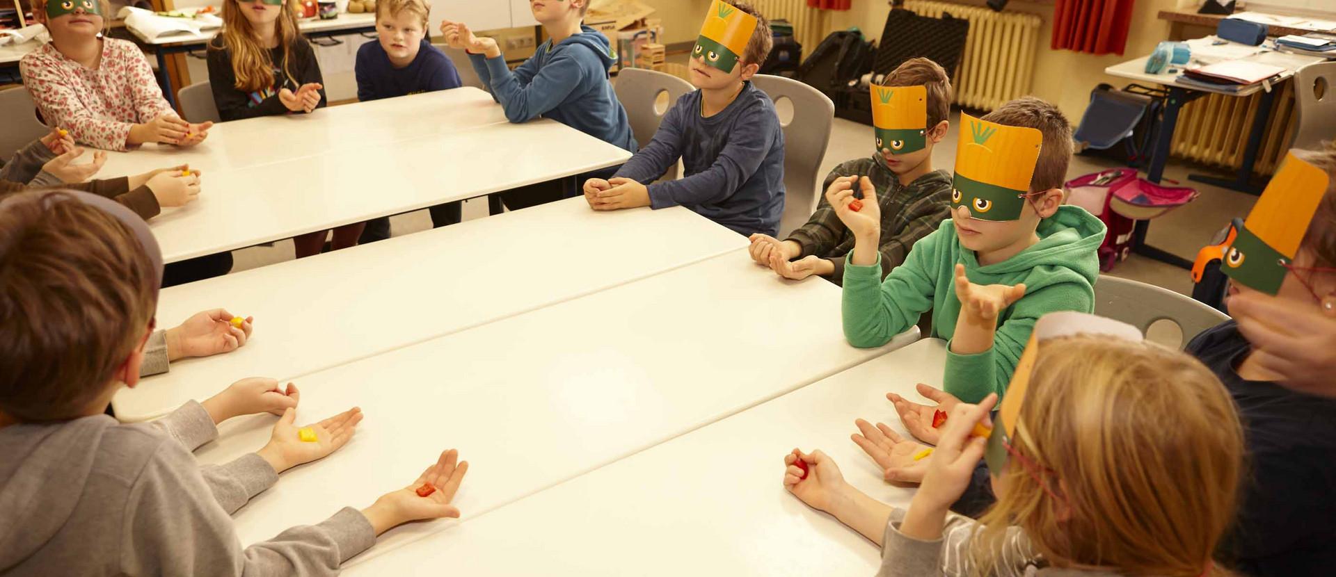 Kinder mit Masken sitzen an Tischen in der Schule und ertasten Lebensmittel