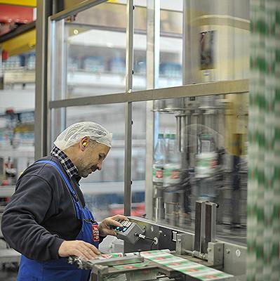 Mitarbeiter stehe an einer Maschine für Flaschentiketten