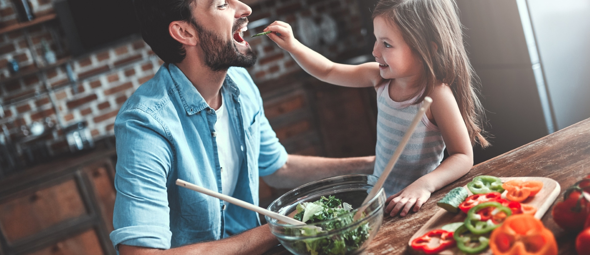 Kind füttert Mann mit Gurke
