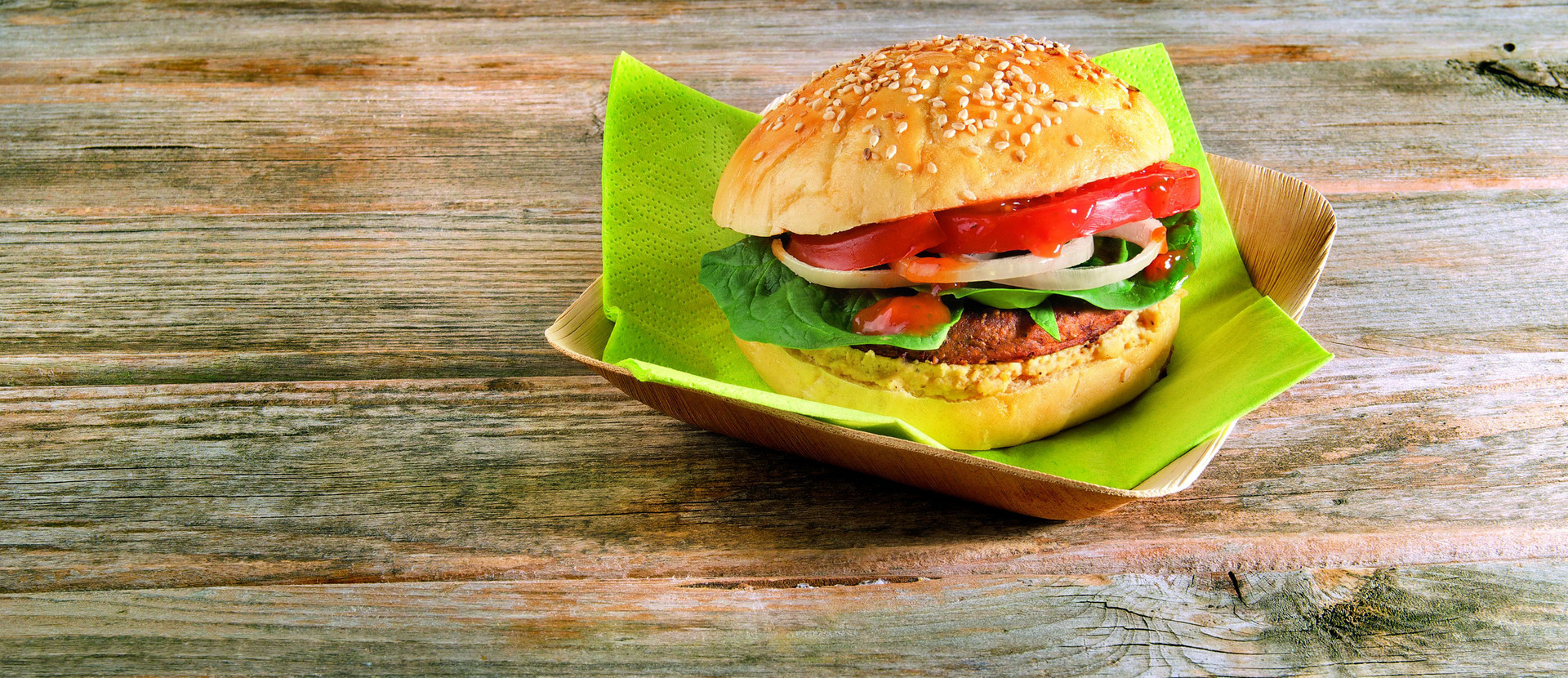 Burger mit Spinat und Hummus auf Holztisch