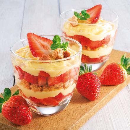 Zwei Gläser auf einem Holzbrett, welche beide abwechselnd mit Schichten von Erdbeeren und einer hellen Creme gefüllt sind