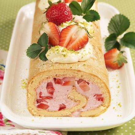 Eine ganze Erdbeer Biskuitrolle mit frischen Erdbeeren und Minzblättern garniert