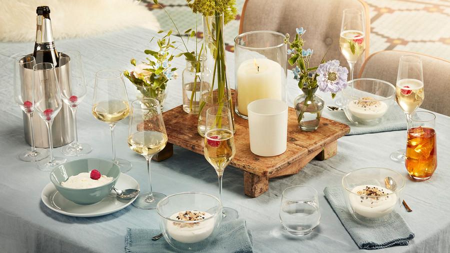 Gläser auf Tisch mit Nachtisch, Kerze, Blumen und Sekt