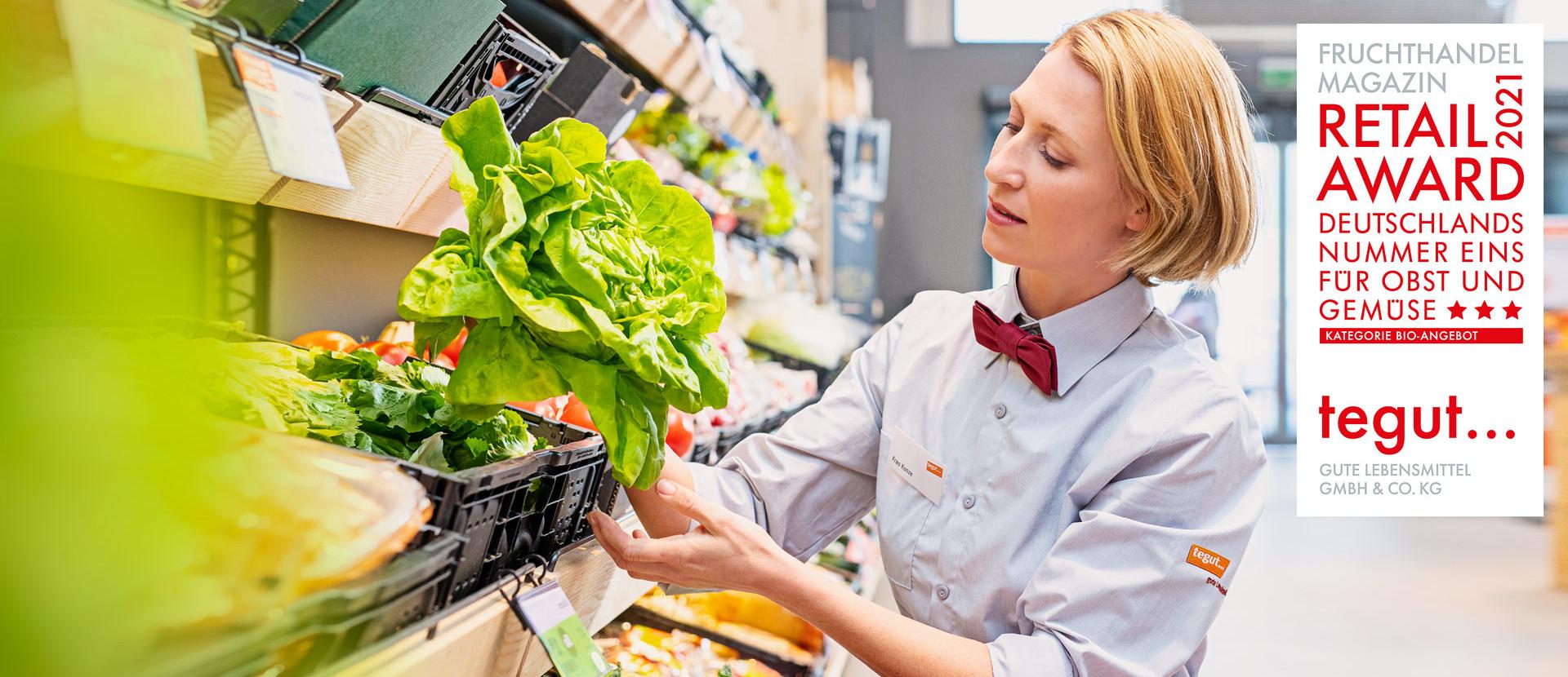 Fruchthandel RetailAward21 Frau räumt Salat in Obstabteilung in Regal