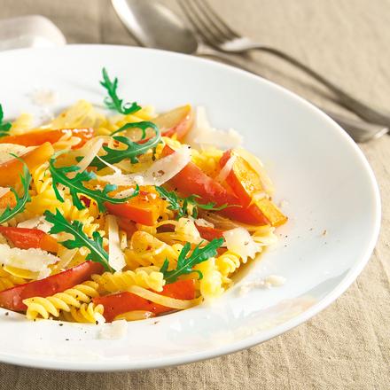 Spirelli mit Kürbisscheiben, Parmesan und Rucolasalat serviert auf einem tiefen weißen Teller der auf einem Leinentuch steht. Lecker!