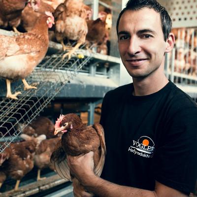 Mann im Hühnerstall mit Huhn auf dem Arm