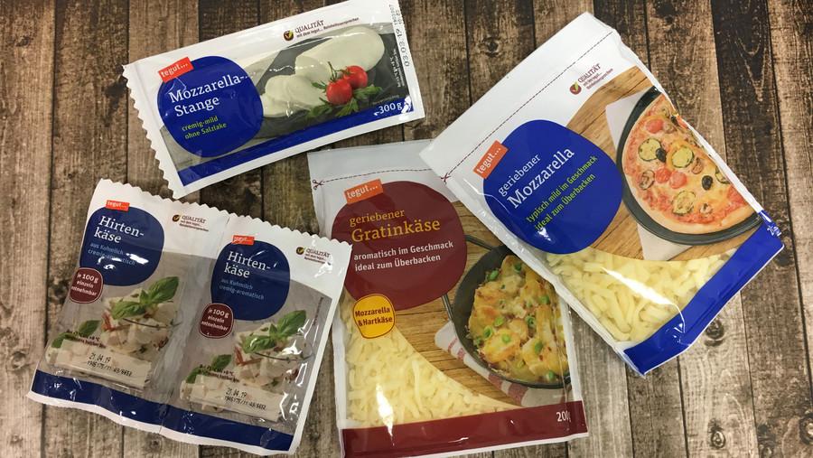 geriebener Mozzarella, Mozzarella-Stange, geriebener Gratinkäse und Hirtenkäse verpackt auf Holzhintergrund