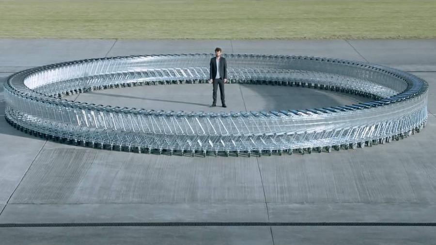 Kreis aus leeren Einkaufswägen auf einem Parkplatz. In der Mitte des Kreises steht ein Mann.