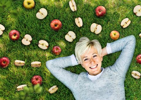 Frau liegt auf Wiese mit Äpfel