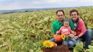 Der Betriebsleiter und die Betriebsleiterin knien mit ihrem Kleinkind auf einem Kürbisfeld und halten eine Sonnenblume in der Hand
