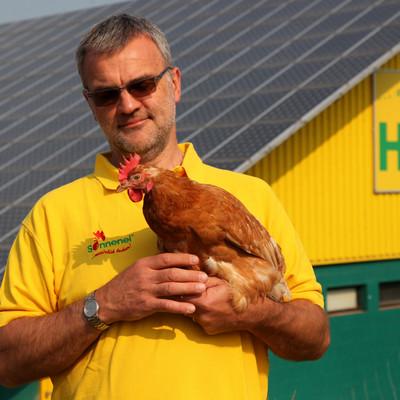 Mann hält Huhn in der Hand