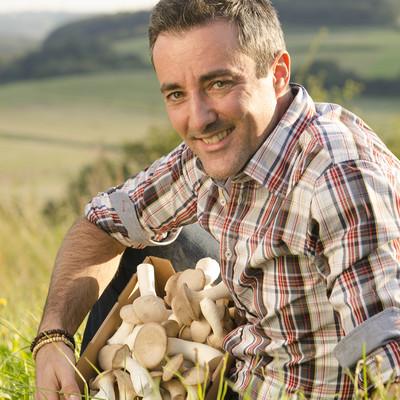 Mann sitzt in einer Wiese und hat einen Karton mit Pilzen in den Händen