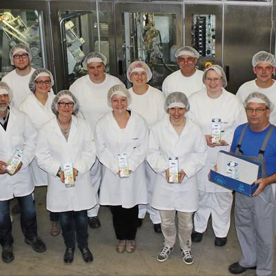 Gruppenbild der Mitarbeiter der Marburger Molkereigenossenschaft mit Milchpackungen in den Händen