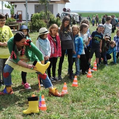 Gruppe Kinder steht auf einer Wiese und macht Gummistiefel-Weitwurf