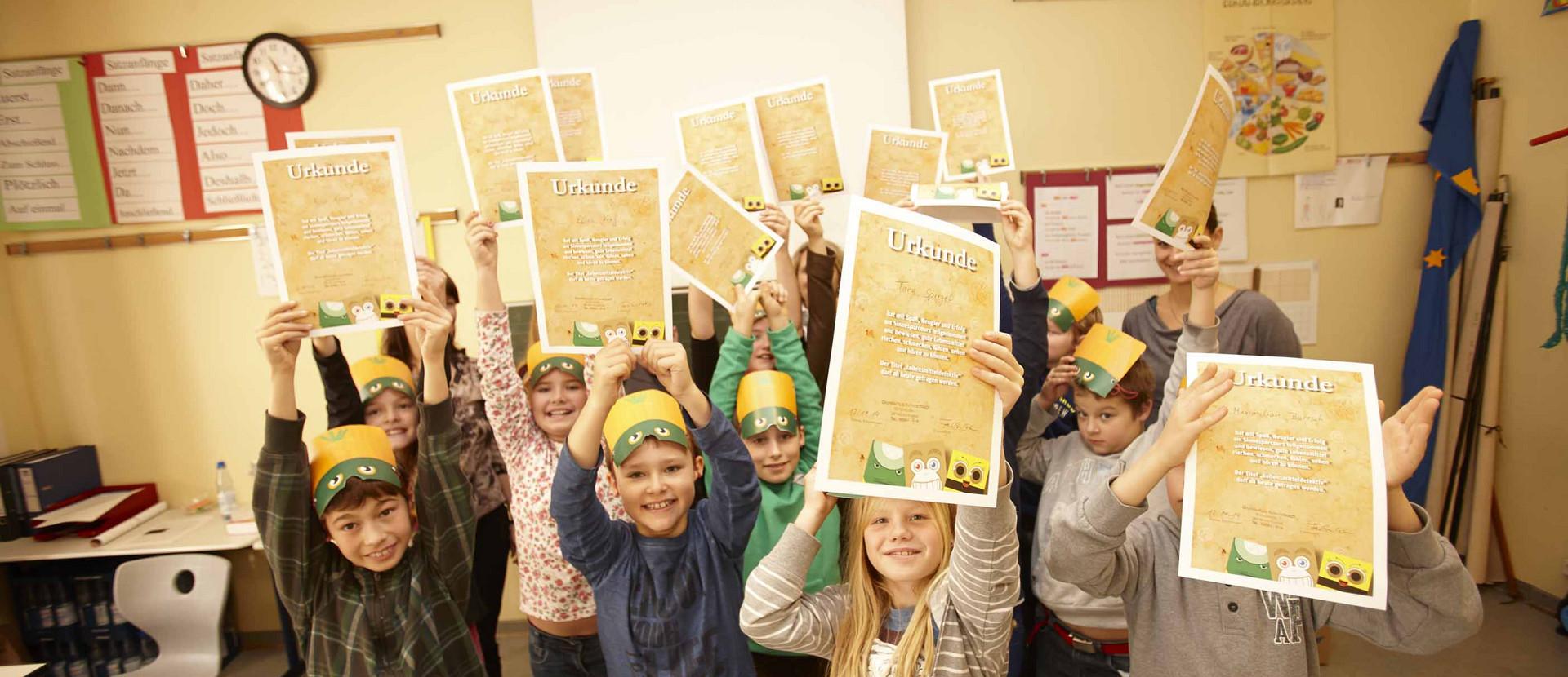 Gruppe Kinder halten Urkunden in die Höhe