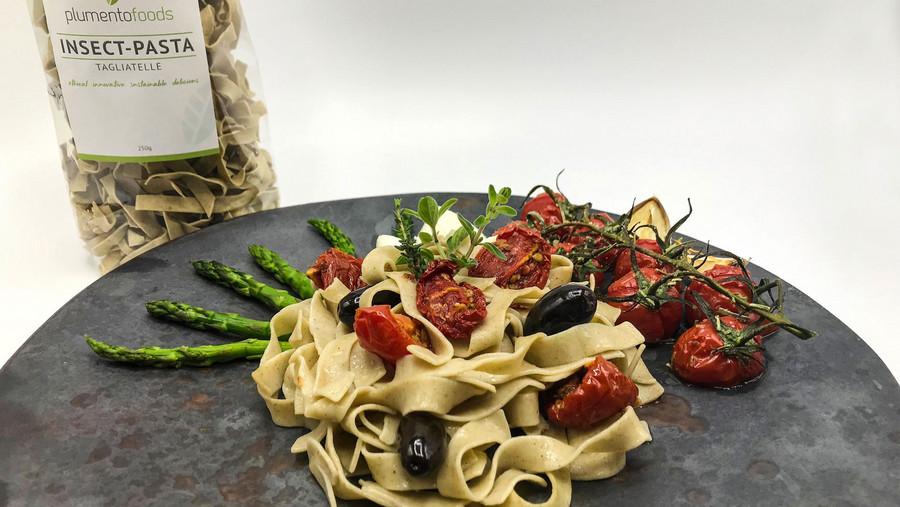 Pasta auf Teller mit Tomaten und Spinat