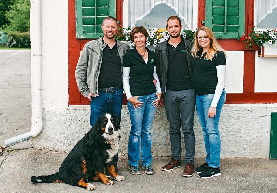 Familie Russ steht vorm Haus mit Hund