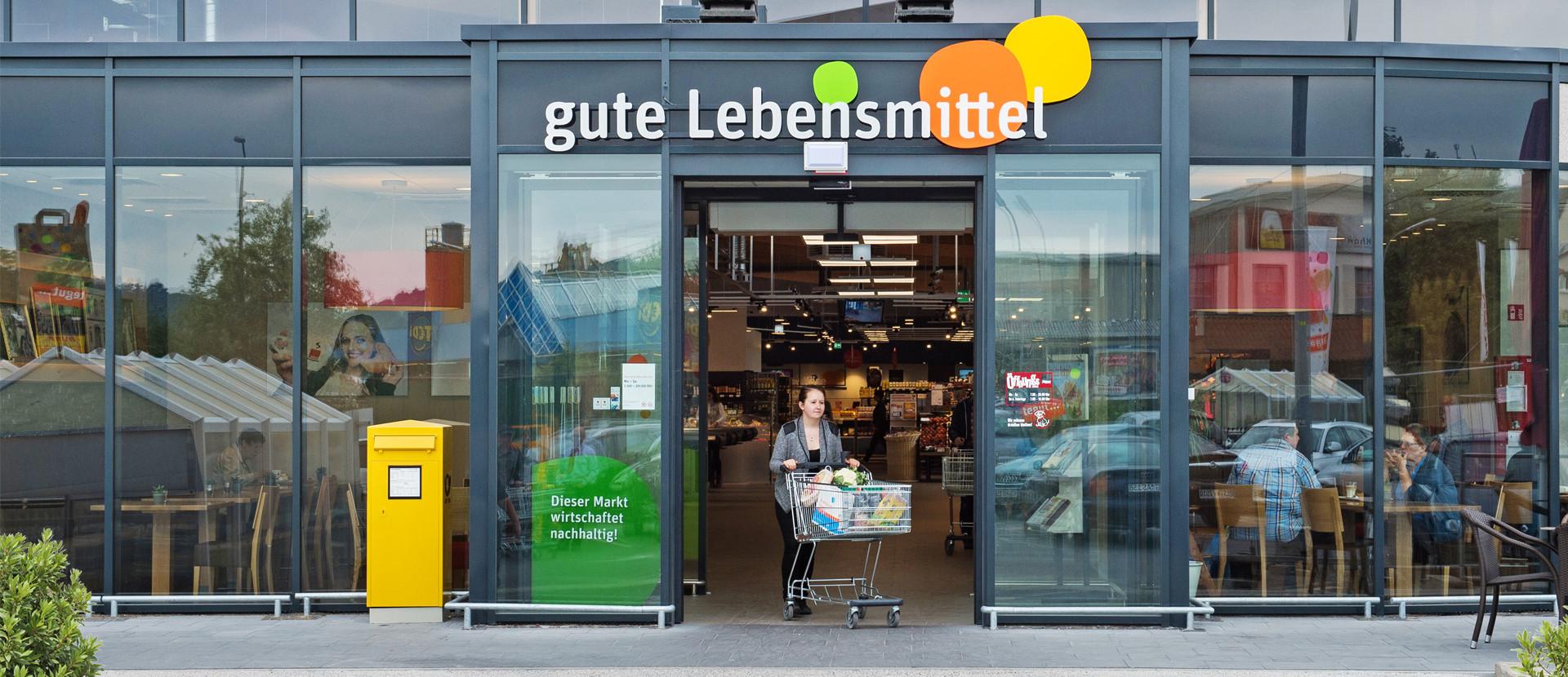 Marktsuche Frau kommt mit Einkaufswagen aus Haupteingang des tegut Markt Bad Neustadt