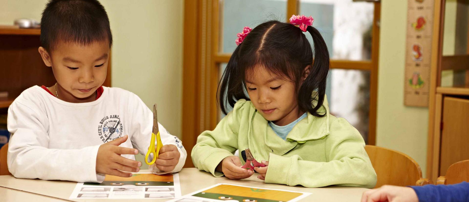 zwei Kinder sitzen an einem Tisch und schneiden aus