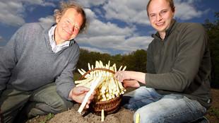 Vater und Sohn sitzen mit einem Korb voll frisch gestochenem Spargel auf dem Acker