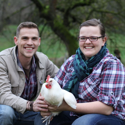 Mann und Frau halten eine Henne