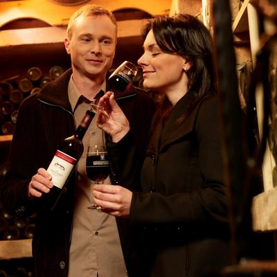 eine Frau riecht an Rotwein in einem Glas, ein Mann steht dahinter mit einer Flasche Wein in der Hand