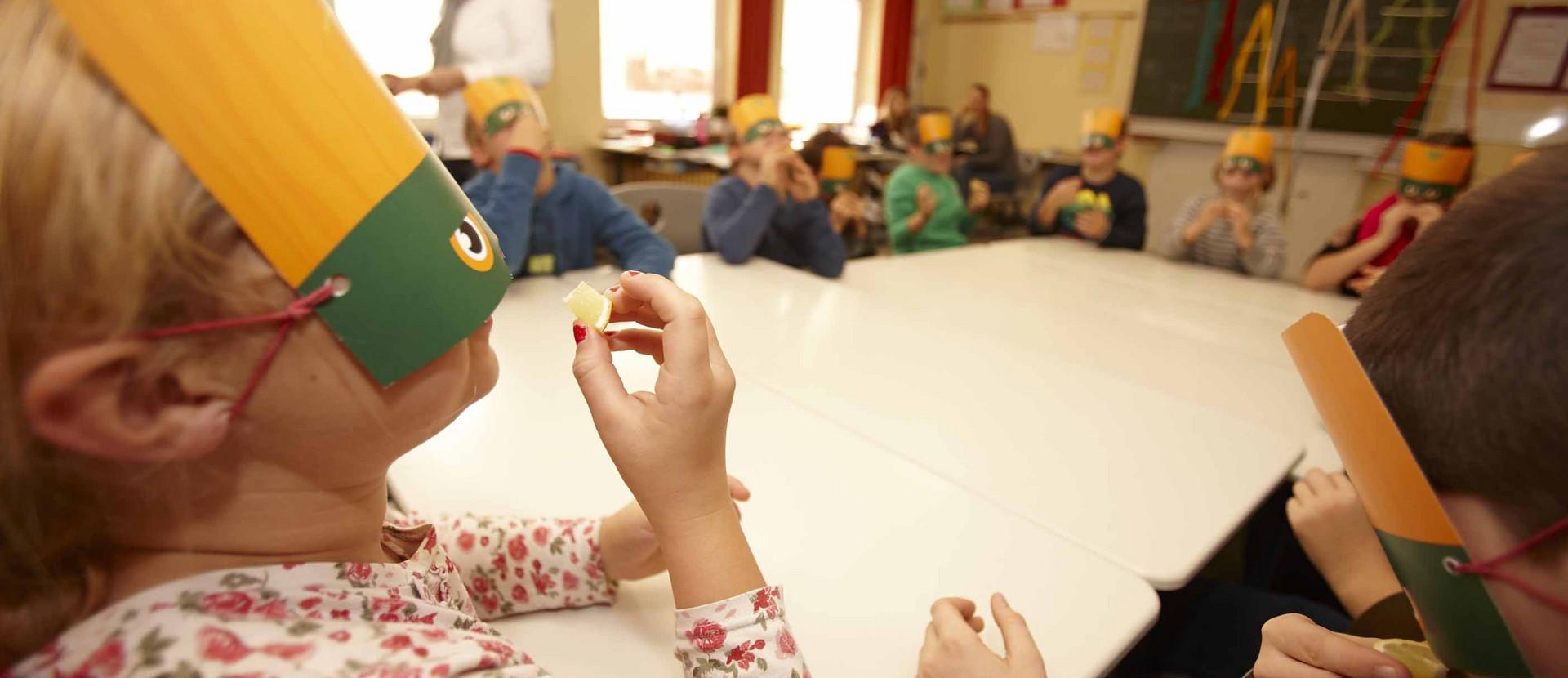 Kinder mit Masken probieren Zitrone