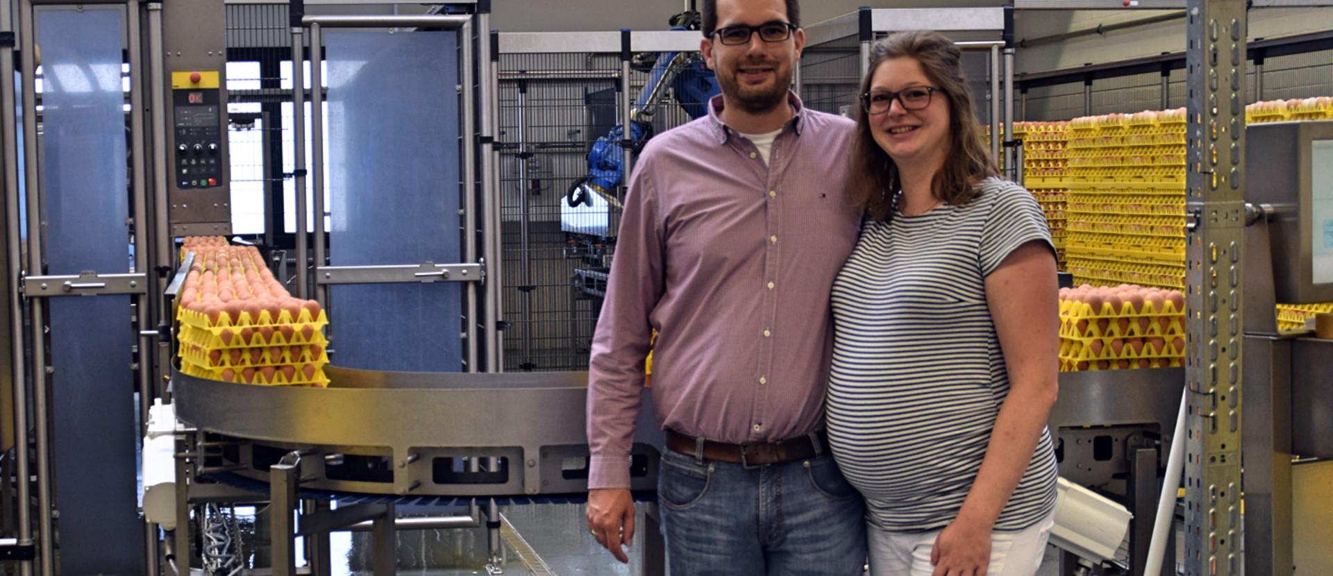 Betriebsleiter und Betriebsleiterin stehen vor einem Förderband, welches Eier in einen Lagerraum transportiert