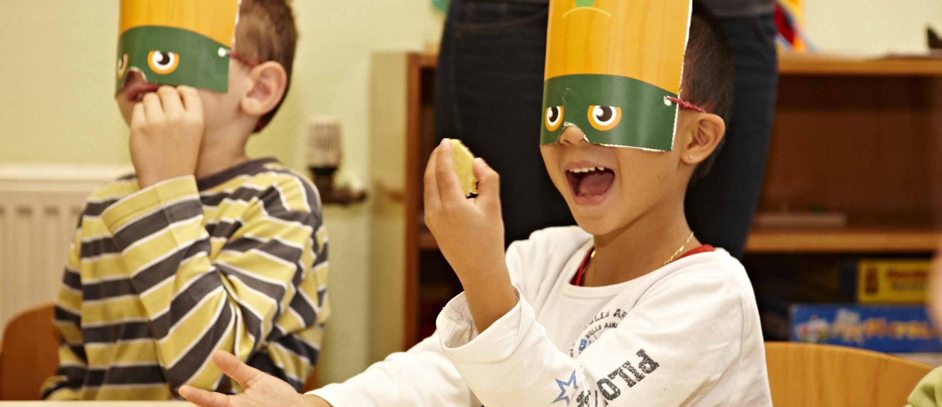 zwei Jungen mit Masken schmecken Lebensmittel