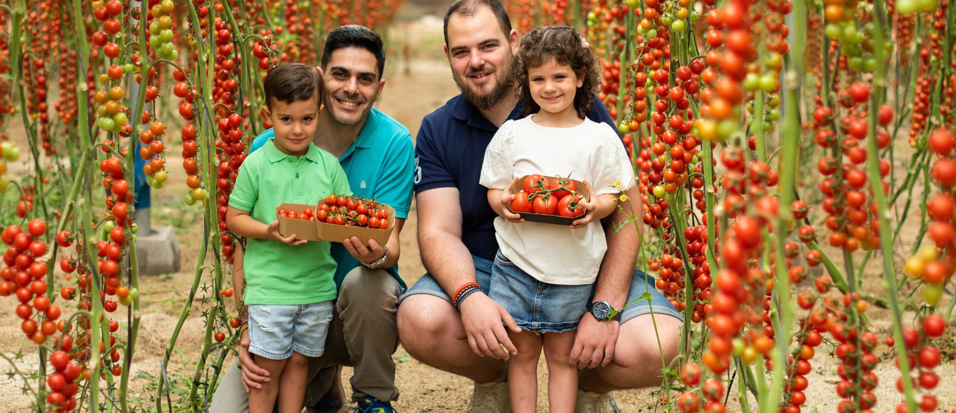 Erzeuger mit mit Kindern vor einer Tomatenplantage in Spanien.