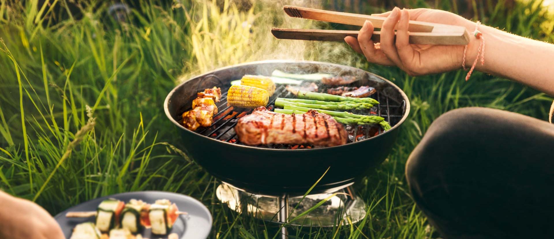 Grill mit Spargel, Steak und Maiskolben steht in Wiese