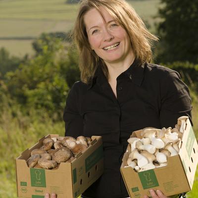 Frau mit zwei Kartons Pilzen in den Händen