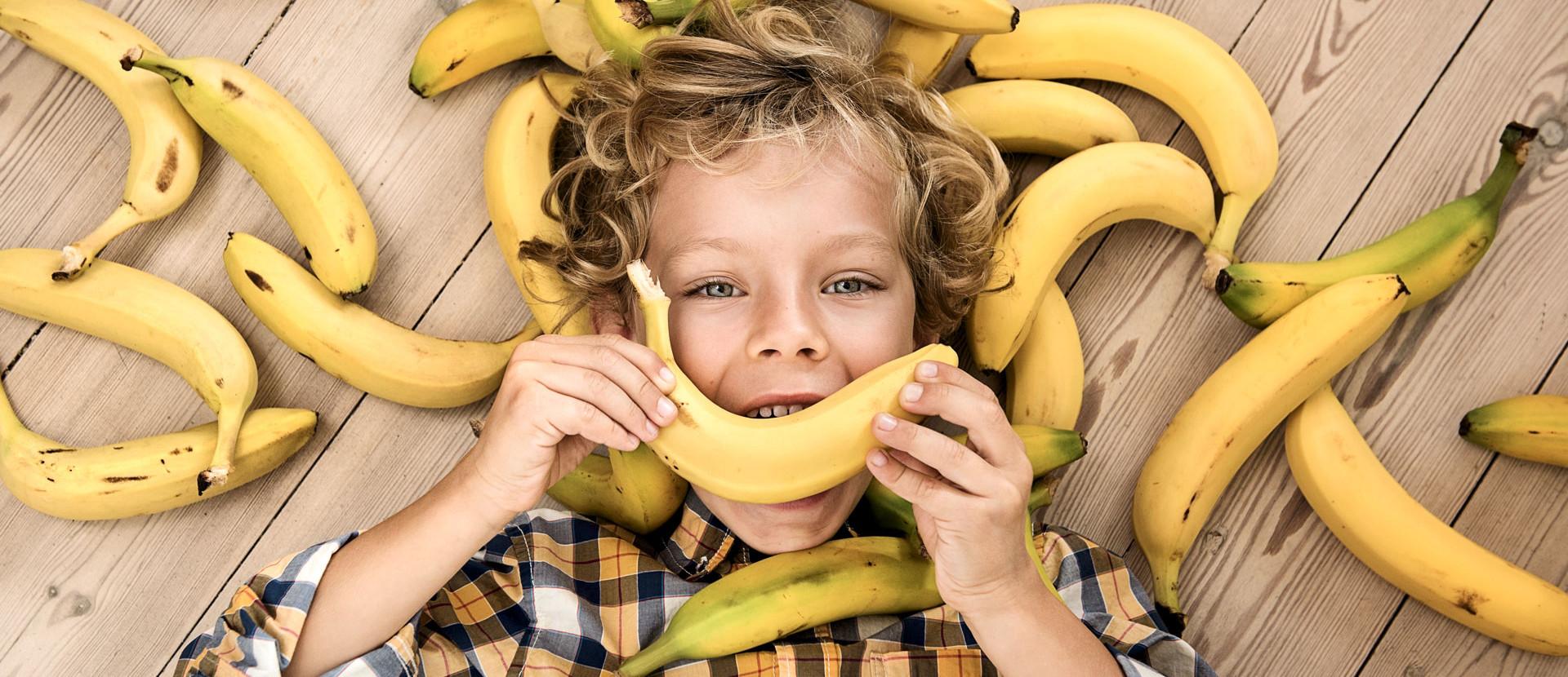 Junge liegt auf Holzboden mit Bananen