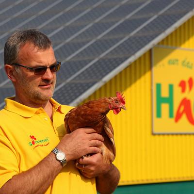 Mann hält Huhn